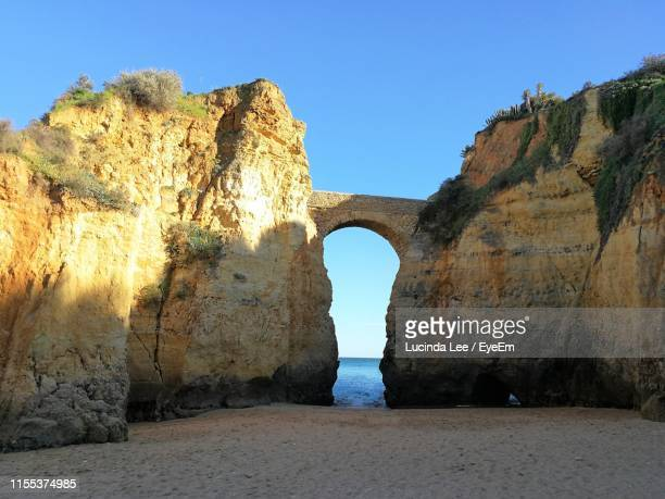 rock formation against clear blue sky - lucinda lee stock photos and pictures