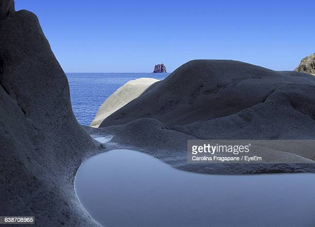 rock formation and sea against blue sky - carolina fragapane stock pictures, royalty-free photos & images