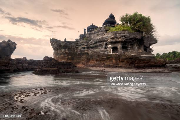 rock formation at beach against sky - tanah lot stock pictures, royalty-free photos & images