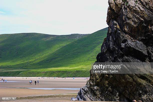rock formation at beach against sky - gower peninsula stock photos and pictures