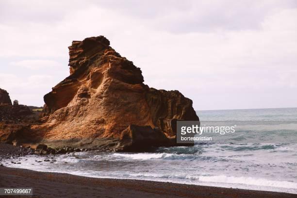 rock formation at sea shore against sky - bortes photos et images de collection