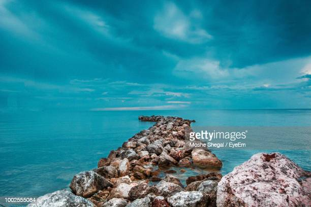 rock formation by sea against blue sky - kingston jamaica stock pictures, royalty-free photos & images