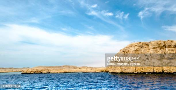rock formation by sea against blue sky - シャルムエルシェイク ストックフォトと画像