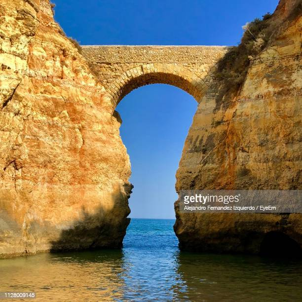 rock formation by sea against clear blue sky - faro district portugal stock pictures, royalty-free photos & images