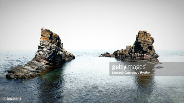 rock formation in sea against clear sky - krasimir georgiev stock photos and pictures