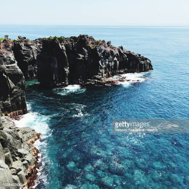 rock formation in sea against sky - rocky coastline stock pictures, royalty-free photos & images