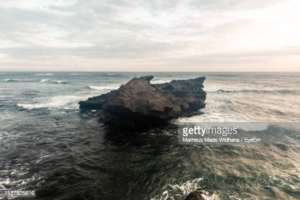 rock formation in sea against sky - made widhana stock photos and pictures