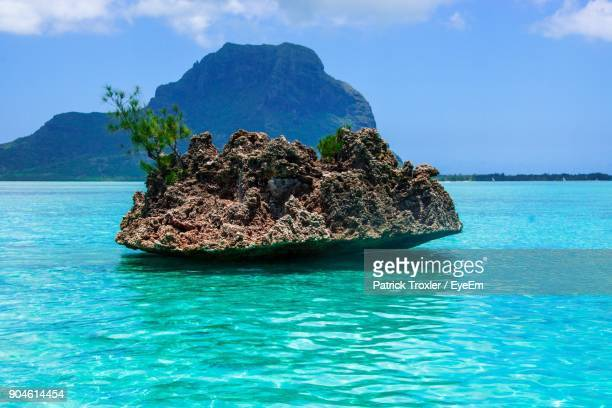 rock formation in sea against sky - port louis stock photos and pictures