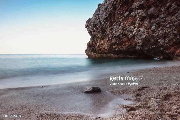 rock formation on beach against clear sky - vaso stock pictures, royalty-free photos & images