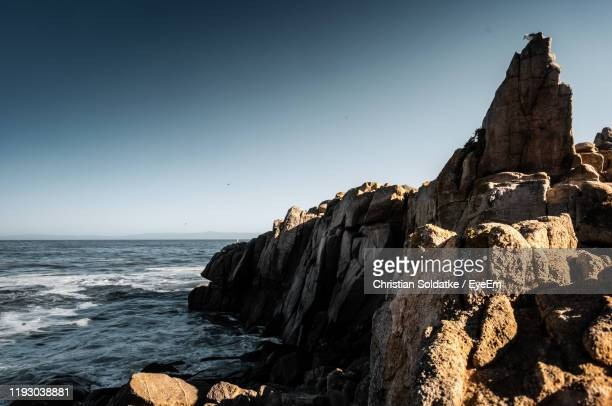 rock formation on beach against clear sky - christian soldatke imagens e fotografias de stock