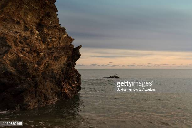 rock formation on beach against sky during sunset - heinovirta stock photos and pictures