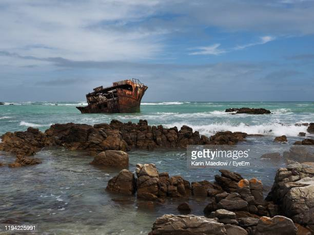 rock formation on beach against sky - afrika afrika stock pictures, royalty-free photos & images