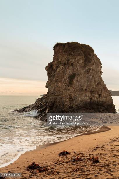 rock formation on beach against sky - heinovirta stock pictures, royalty-free photos & images