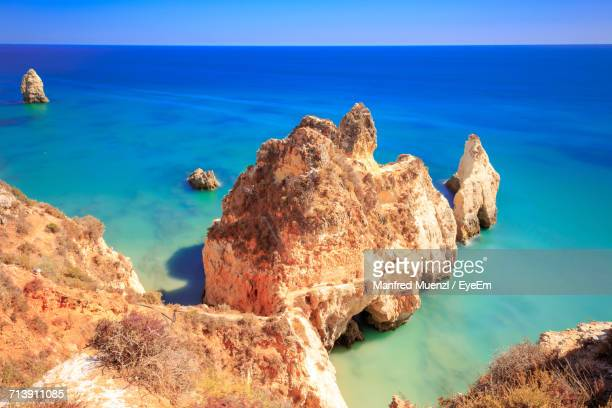 rock formation on beach against sky - alvor stock pictures, royalty-free photos & images
