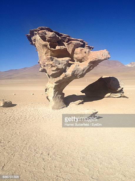 rock formation on field in desert against clear blue sky during sunny day - harriet stock photos and pictures