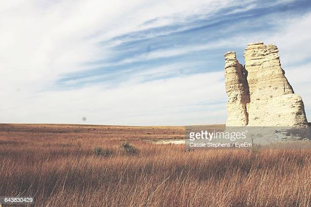 rock formation on grassy field against sky - wichita stock photos and pictures