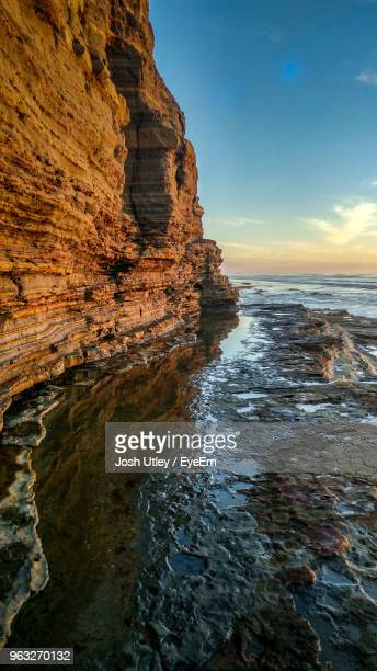 rock formation on sea against sky during sunset - josh utley stock pictures, royalty-free photos & images
