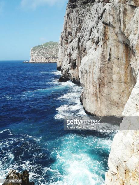 rock formation on sea shore against blue sky - aneta eyeem stock pictures, royalty-free photos & images