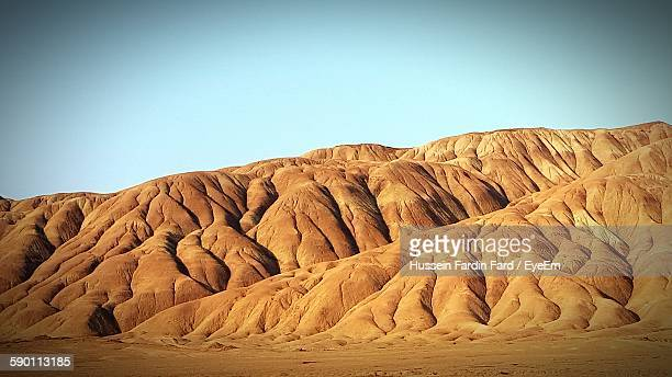 rock formations at desert against clear sky - isfahan stock-fotos und bilder
