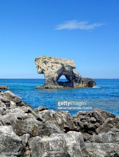 rock formations by sea against blue sky - erosion stock pictures, royalty-free photos & images