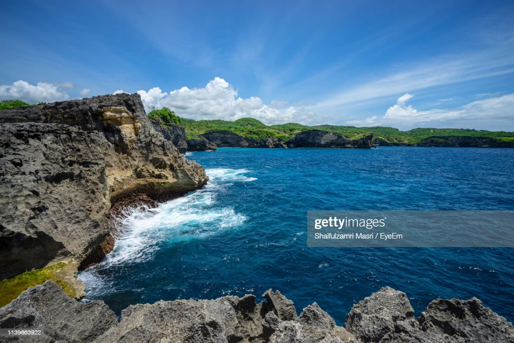 Rock Formations By Sea Against Blue Sky : Stock Photo