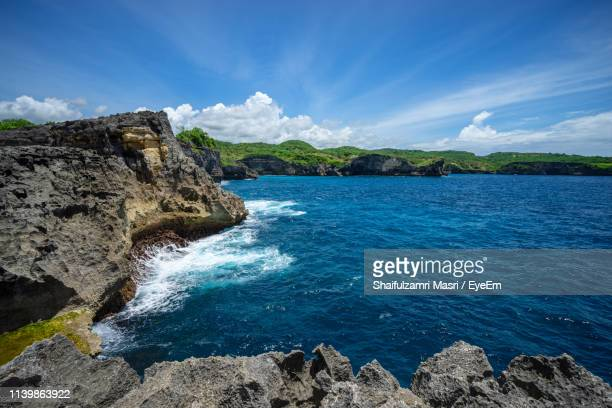 rock formations by sea against blue sky - shaifulzamri stock pictures, royalty-free photos & images