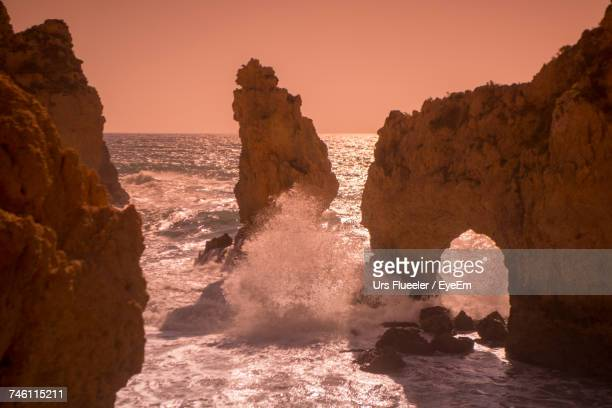 Rock Formations By Sea Against Clear Sky During Sunset