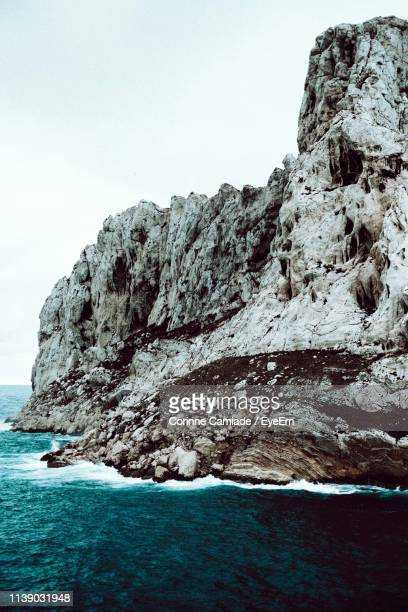 rock formations by sea against clear sky - corinne paradis ストックフォトと画像