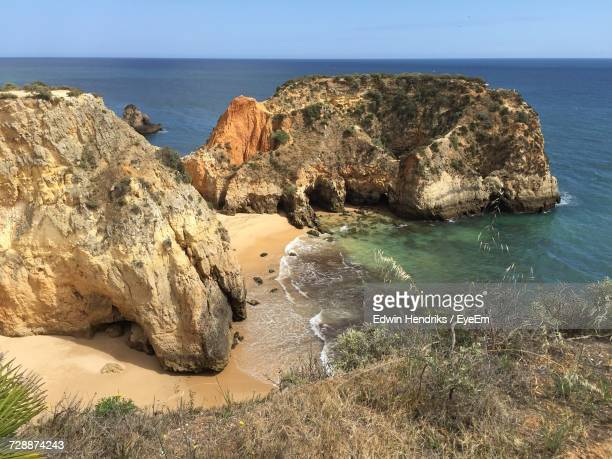 rock formations by sea against clear sky - alvor stock pictures, royalty-free photos & images