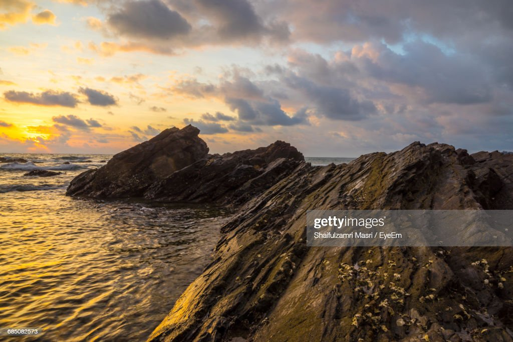 Rock Formations By Sea Against Cloudy Sky During Sunset : Stock Photo
