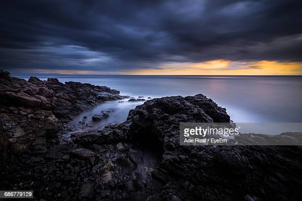rock formations by sea against cloudy sky during sunset - ade rizal stock photos and pictures