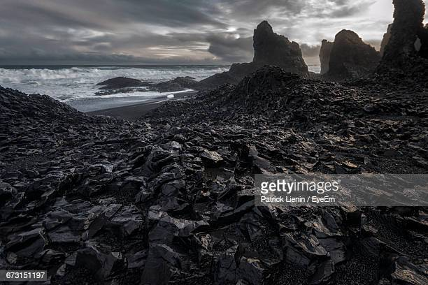 rock formations by sea against cloudy sky - rock formation stock pictures, royalty-free photos & images