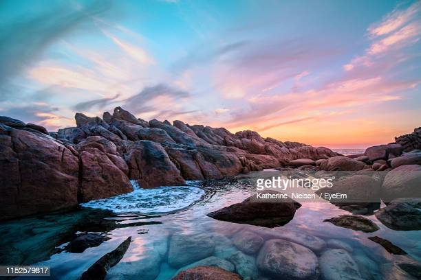rock formations by sea against sky during sunset - western australia stock pictures, royalty-free photos & images