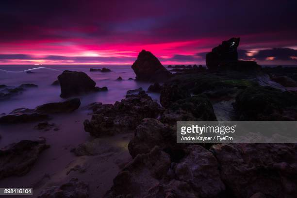 rock formations by sea against sky during sunset - nazar stock photos and pictures