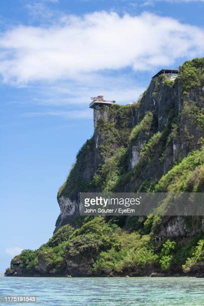 rock formations by sea against sky - guam stock pictures, royalty-free photos & images