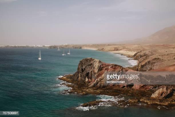 rock formations by sea against sky - bortes fotografías e imágenes de stock