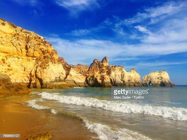 rock formations by sea against sky - alvor stock pictures, royalty-free photos & images