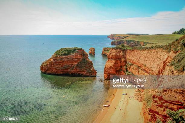 rock formations by sea against sky - devon stock pictures, royalty-free photos & images