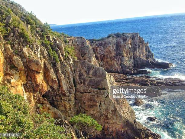 rock formations by sea against sky - rocky coastline stock pictures, royalty-free photos & images