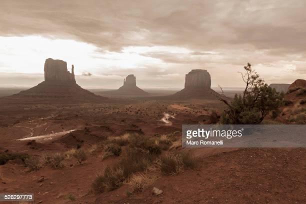 Rock formations in desert under cloudy sky, Monument Valley, Utah, United States