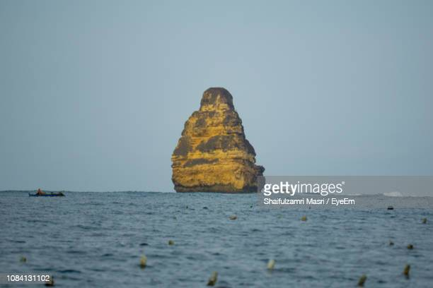 rock formations in sea against clear blue sky - shaifulzamri stock pictures, royalty-free photos & images
