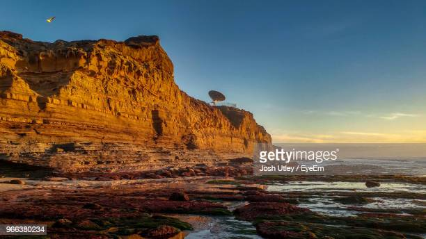 rock formations in sea against sky during sunset - josh utley stock pictures, royalty-free photos & images
