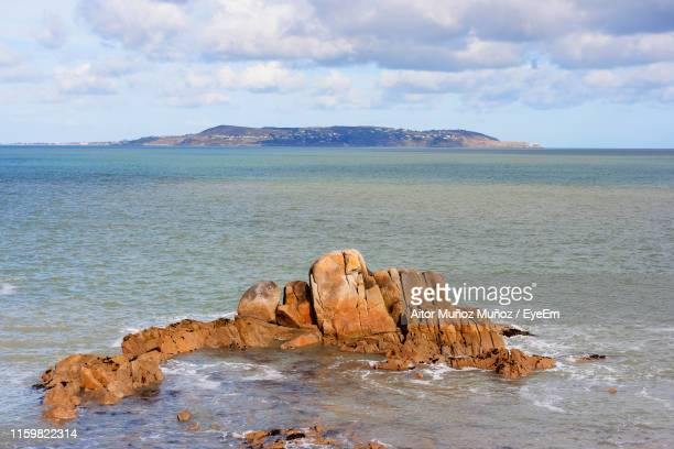 rock formations in sea against sky - dalkey stock pictures, royalty-free photos & images