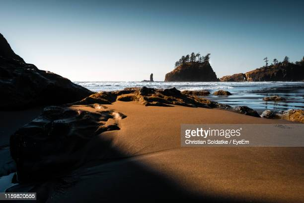 rock formations on beach against clear sky - christian soldatke stock pictures, royalty-free photos & images