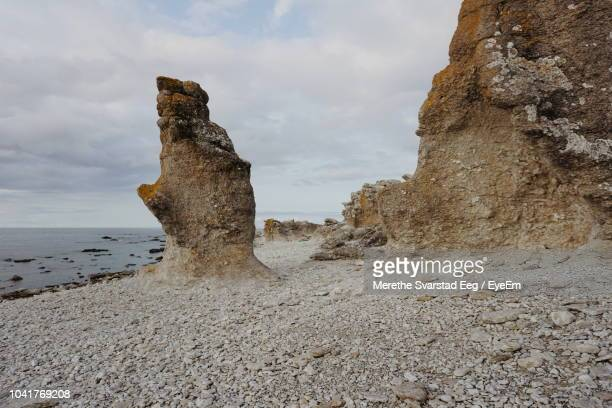 rock formations on beach against sky - rock formation stock pictures, royalty-free photos & images