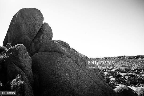 Rock Formations On Field Against Sky