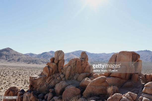 rock formations on landscape against sky - muro stock photos and pictures