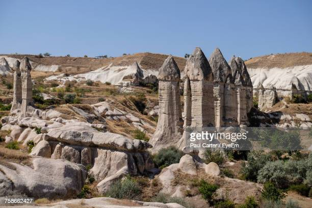 rock formations on landscape against sky - rock hoodoo stock pictures, royalty-free photos & images