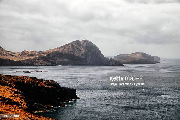 Rock Formations On Sea Against Cloudy Sky