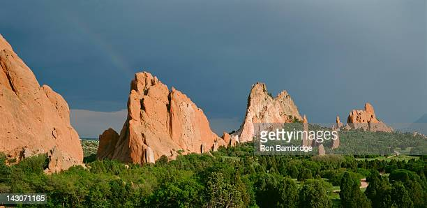 rock formations reaching up through forest - garden of the gods stock photos and pictures
